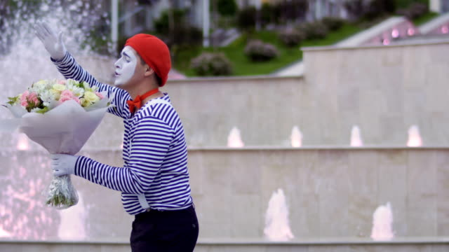 cute mime in red beret has fun with bouquet of flowers - гримировальные краски стоковые видео и кадры b-roll