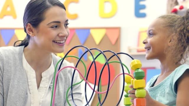 귀여운 혼혈 여성 유치원 학생 연극 구슬 미로 - 대체 요법 스톡 비디오 및 b-롤 화면