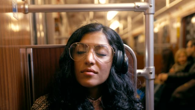 cute mixed race girl listening to music on the subway - music filmów i materiałów b-roll