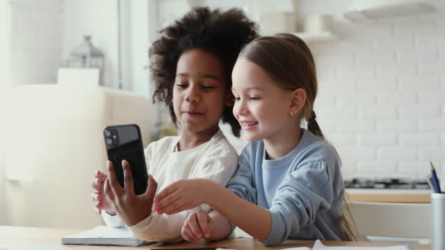 Cute mixed race kids girls playing with smart phone together