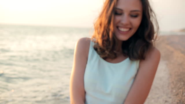 cute model with a beautiful smile laughing and walking along the beach in the summer - beach fashion stock videos and b-roll footage