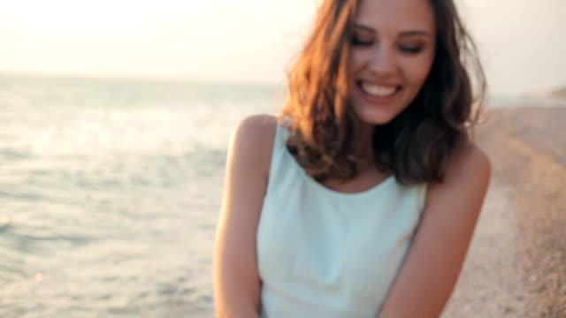 hübsches modell mit einem schönen lächeln, lachen und zu fuß am strand im sommer - strandmode stock-videos und b-roll-filmmaterial