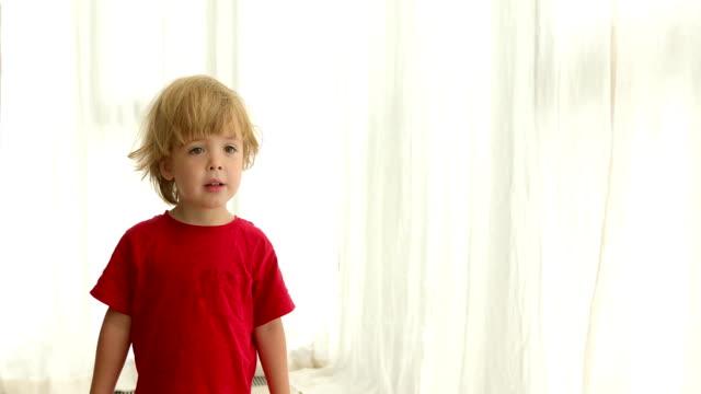 Cute modern boy standing in room