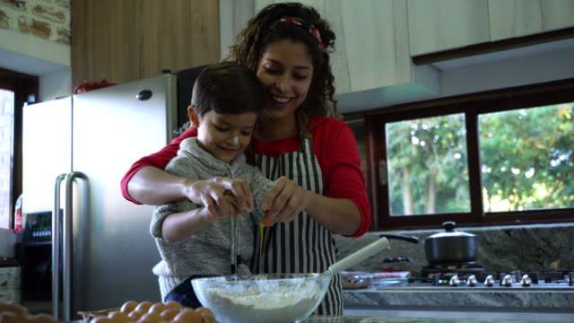 vídeos de stock e filmes b-roll de cute mother and son baking a christmas cake together breaking an egg in bowl at home - christmas cooking