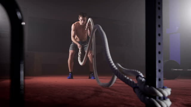 Cute muscular man doing gym rope double wave exercise at the gym