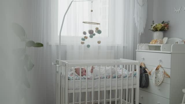 vídeos de stock, filmes e b-roll de bebê recém-nascido fofo deitado no berço no quarto moderno brilhante - mobile