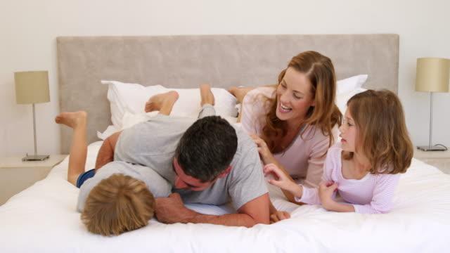 ładny rodziców i dzieci, a rodzinna anegdota głosi i łaskotać siebie - kołdra filmów i materiałów b-roll