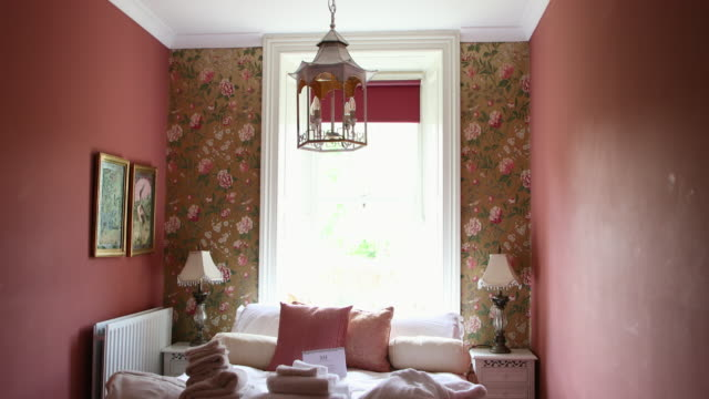 Cute Pink Bedroom A panning shot of a classical style pink, floral bedroom in a luxury hotel. floral pattern stock videos & royalty-free footage