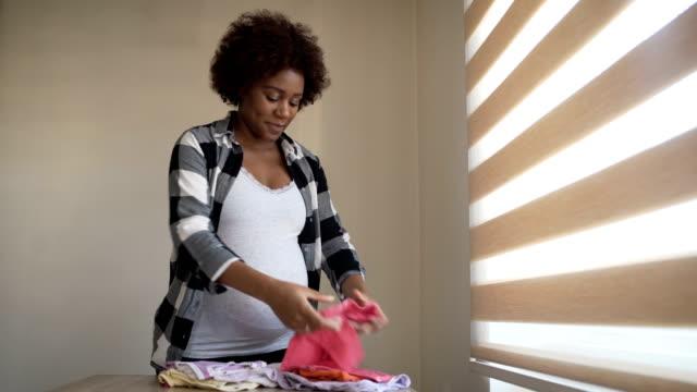 vídeos y material grabado en eventos de stock de linda joven embarazada se prepara para el parto del bebé, buscando ropa para un bebé - nuevo bebé