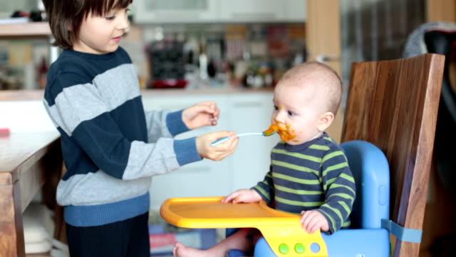 かわいい就学前の男の子、マッシュ野菜で彼の赤ちゃんの弟を養う、赤ちゃんは初めてマッシュフードを食べる - 兄弟姉妹点の映像素材/bロール