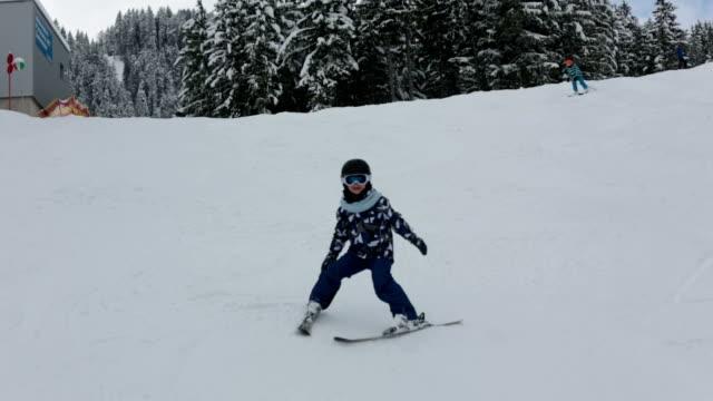 cute preschool children, skiing in austrian winter resort on a clear day, wintertime - stato federato del tirolo video stock e b–roll