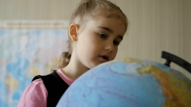 Cute pupil looking at globe in library at the elementary school. Travel planning. Little girl looking at the globe at home in room. Student Child Studying Earth Globe in Library. Closeup.