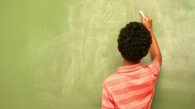 Cute pupil writing maths on chalkboard video
