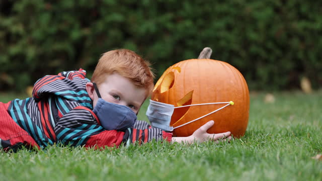 Cute redhead boy looking a Jack O' Lantern while lying down on grass and wearing wearing protective mask