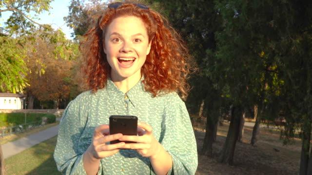Cute redhead girl using phone