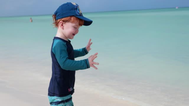 cute redhead toddler dancing on beach - кепка стоковые видео и кадры b-roll