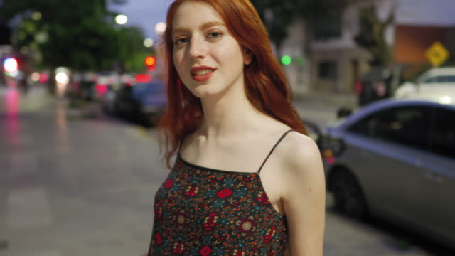 Cute redhead woman with freckles on city street at night video