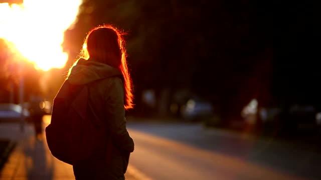 stockvideo's en b-roll-footage met leuk roodharige meisje permanent in de straten - bushalte