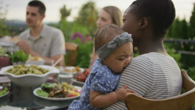 cute restless baby at an outdoor dinner party - nigeria video stock e b–roll