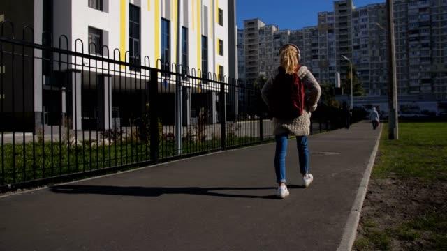 Linda colegiala con mochila a la escuela - vídeo