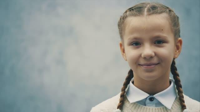stockvideo's en b-roll-footage met schattige schoolkid kijkt naar de camera met nieuwsgierige ogen. - portrait background