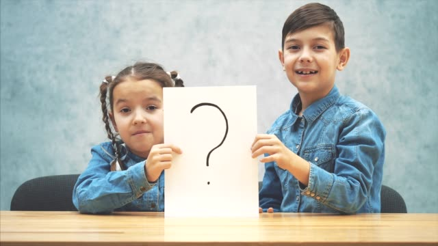 cute schoolkids sitting at th desk, holding a sheet of paper with the exclamation mark written on it, having no idea what it means. asking face expressions. - communication problems stock videos & royalty-free footage