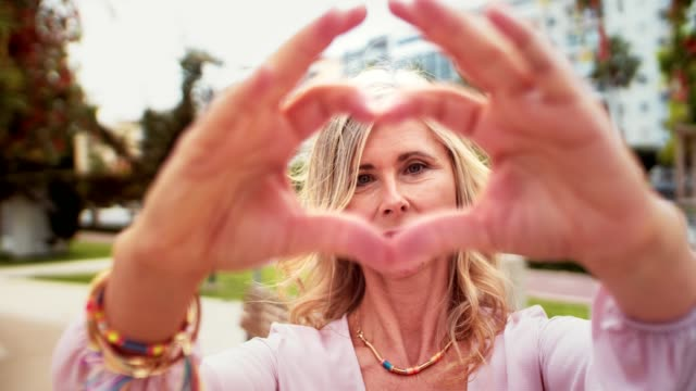 Cute senior woman making a heart-shape with her hands Beautiful mature woman standing in city park making a heart shape symbol with her hands gesturing stock videos & royalty-free footage