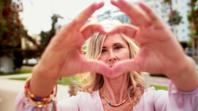 cute senior woman making a heart-shape with her hands - gestykulować filmów i materiałów b-roll