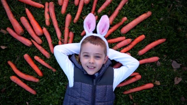 niedlich heiteres kind, das mit kaninchen auf dem boden liegt - karotte peace stock-videos und b-roll-filmmaterial