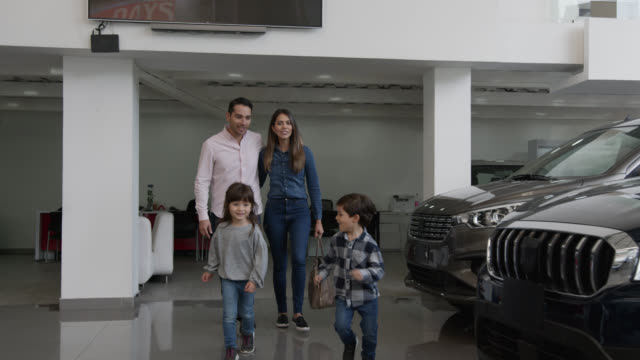 Cute siblings running at a car dealership towards a car they liked pointing it to loving mom and dad