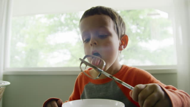 vídeos y material grabado en eventos de stock de un lindo niño de seis años de raza blanca licks bateador fuera de un beater cableado (de un mezclador de mano eléctrica) en una mesa de cocina en el interior durante el día - memorial day