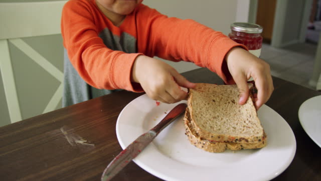 a cute six year-old caucasian boy puts two halves of a peanut butter and jelly sandwich together on a plate and then picks it up and takes a bite out of it at a kitchen table indoors - dżem filmów i materiałów b-roll