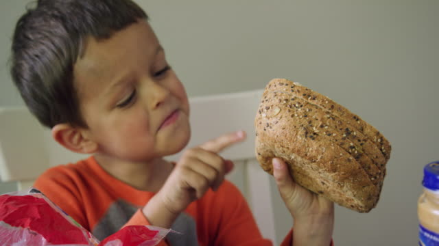 A Cute Six Year-Old Caucasian Boy Removes Several Pieces of Bread from the Loaf Bag and Uses His Finger to Count Them in Preparation for Making a Sandwich While Acting Playful at a Kitchen Table