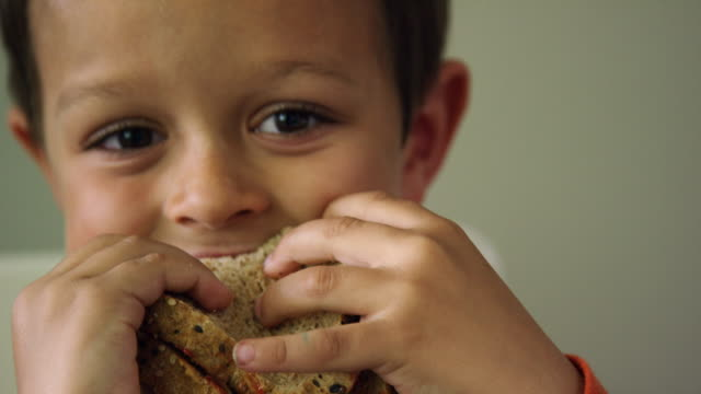 a cute six year-old caucasian boy shows the camera a bite mark in his sandwich before biting it again and smiling - dżem filmów i materiałów b-roll