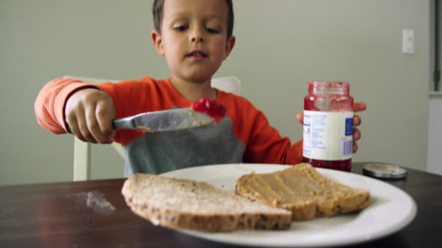 vídeos de stock e filmes b-roll de a cute six year-old caucasian boy unscrews a jar of jelly and then uses a kitchen knife to scoop jelly from the jar and then to spread it on to a piece of bread sitting on a plate while making a peanut butter and jelly sandwich at a kitchen table indoors - jam jar