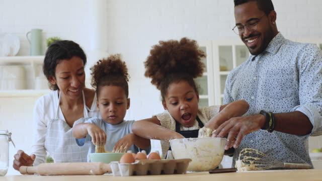 cute small african kids kneading dough helping parents in kitchen - piec przygotowywać jedzenie filmów i materiałów b-roll