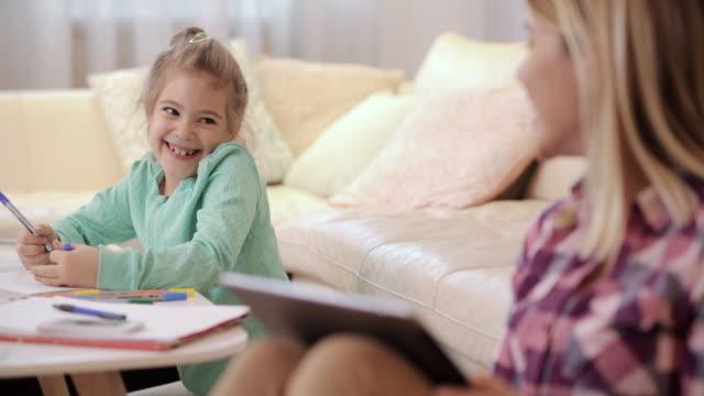 かわいい小さな女の子を家庭で引くと彼女の母親との通信。 ビデオ