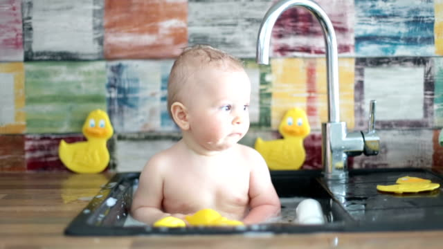 Cute snmiling baby taking bath in kitchen sink. Child playing with foam and soap bubbles in sunny kitchen with rubber ducks, little boy bathing, fun with water.