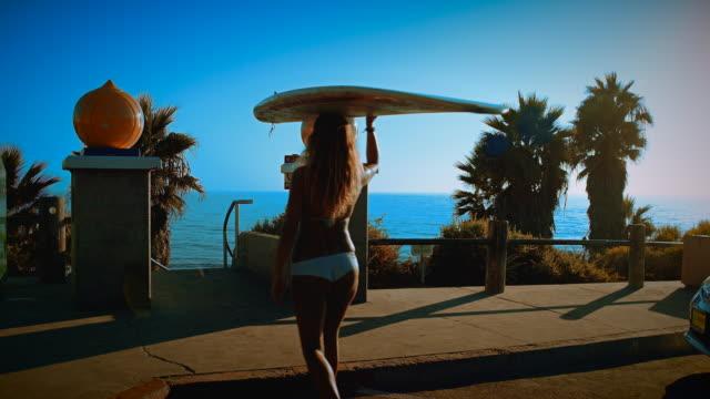 A cute surfer girl walks down to the beach carrying her surfboard, wearing a cute bikini in the summer sun. video