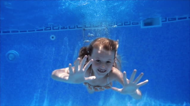 cute swimming girl in slowmotion - solo una bambina femmina video stock e b–roll