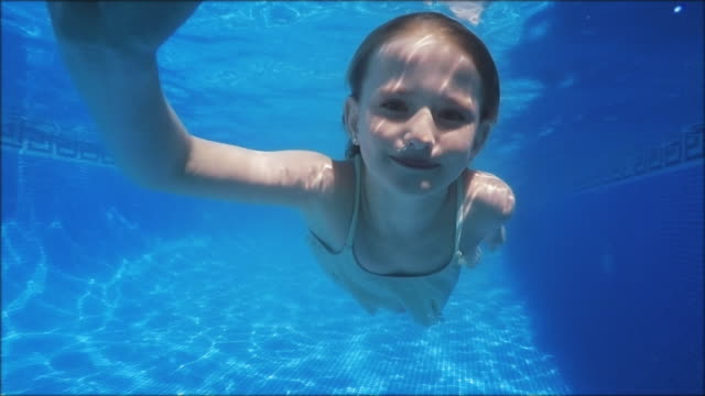 Cute swimming girl in slowmotion video