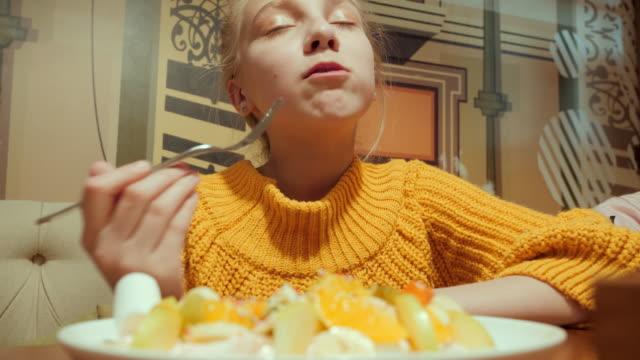 Cute teen girl eating sweet dessert in cafe