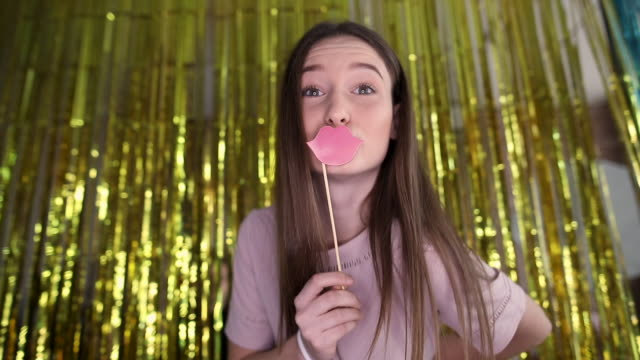 Cute teenage girl having fun with lips prop and taking selfie on photo booth