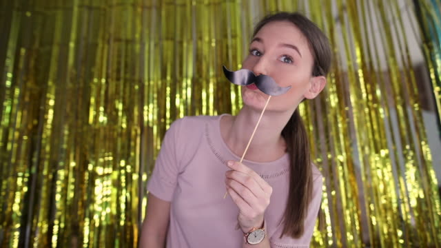 Cute teenage girl having fun with mustache prop and taking selfie on photo booth