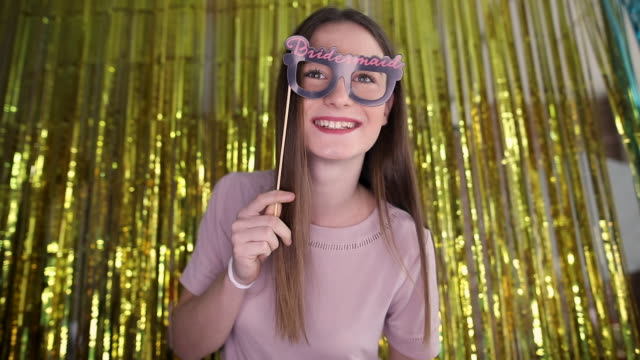 Cute teenage girl having fun with prop and taking selfie on photo booth