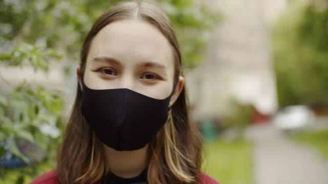 vidéos et rushes de adolescente mignonne souriant derrière le masque protecteur à l'extérieur - 18 19 ans