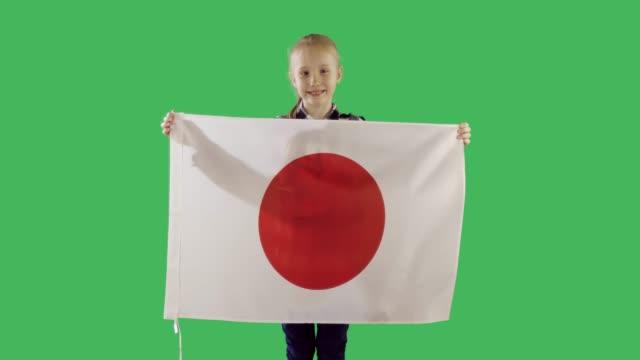 Cute teenager girl holding a Japanese flag on chroma key green screen.
