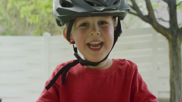 A Cute Three Year-Old Caucasian Boy Wearing a Bicycle Helmet Smiles and Laughs Outdoors while Standing Over His Bike A Cute Three Year-Old Caucasian Boy Wearing a Bicycle Helmet Smiles and Laughs Outdoors while Standing Over His Bike handlebar stock videos & royalty-free footage