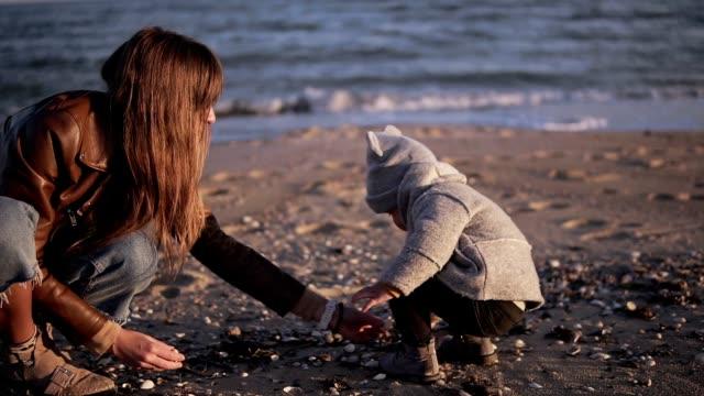 vidéos et rushes de l'enfant en bas âge mignon et la mère passent le temps ensemble et recherchent, ramassant et recueillant des coquilles de mer au bord de mer de plage de sable. temps frais - coquille et coquillage