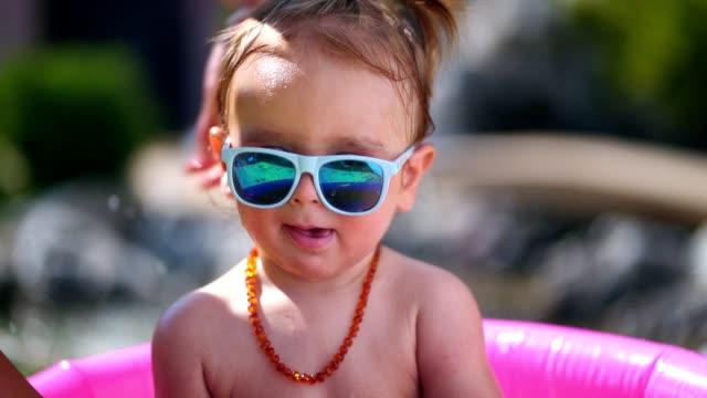 cute toddler boy in inflatable pool - neonati maschi video stock e b–roll